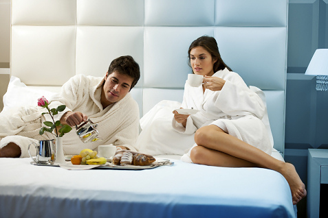 attractive couple eating in luxury bed